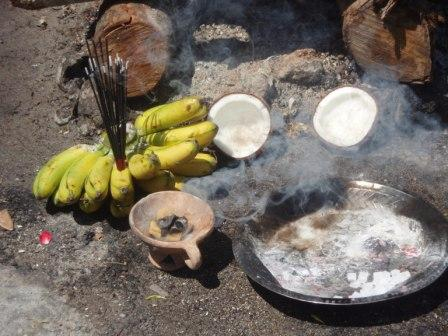 A bunch of bananas, a coconut split in two, an urn bearing burning camphor and a stainless steel dish bearing holy ash and camphor